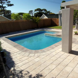 C.E.L. Paving Products Grey Blocks in Lava finish with Grey Surefoot coping surrounding a pool