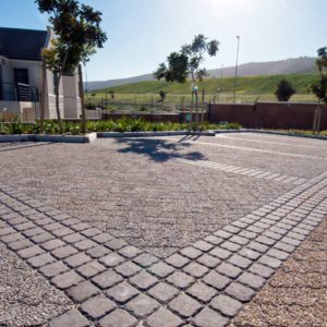 Cobbles frame exposed aggregate driveway pavers